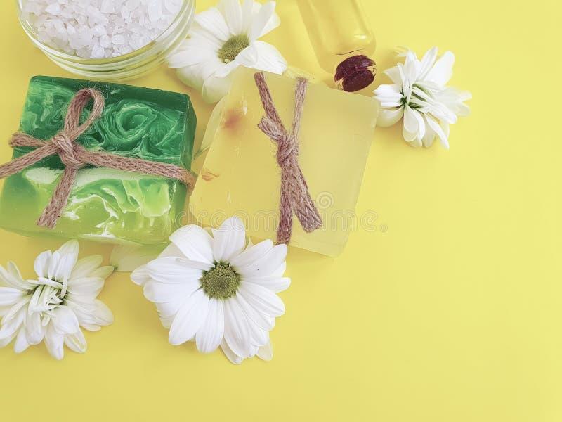 Savon, sel, huile, hygiène organique de fleur d'extrait de chrysanthème sur un fond jaune photographie stock