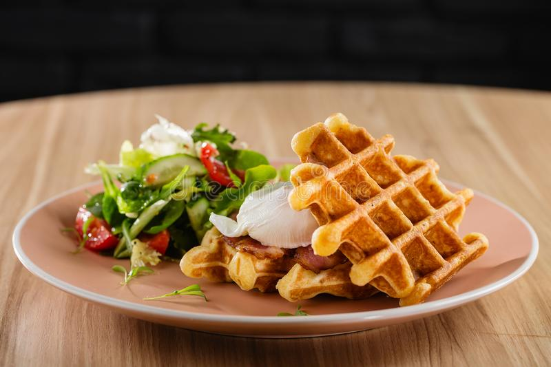 Savory Belgian waffles with egg poached, bacon and salad. Eggs Benedict - American breakfast. Restaurant menu or recipe concept. Copy space stock photo