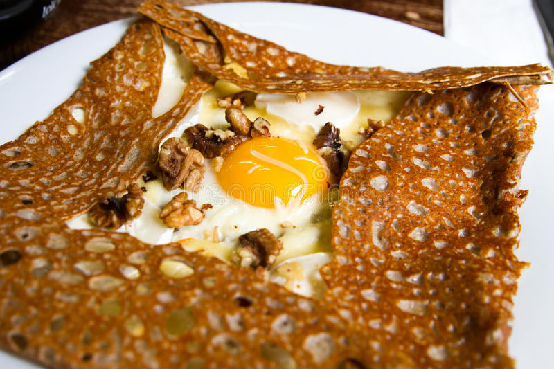 Savory crepe. With fried eggs, cheese and nuts on white plate stock photography