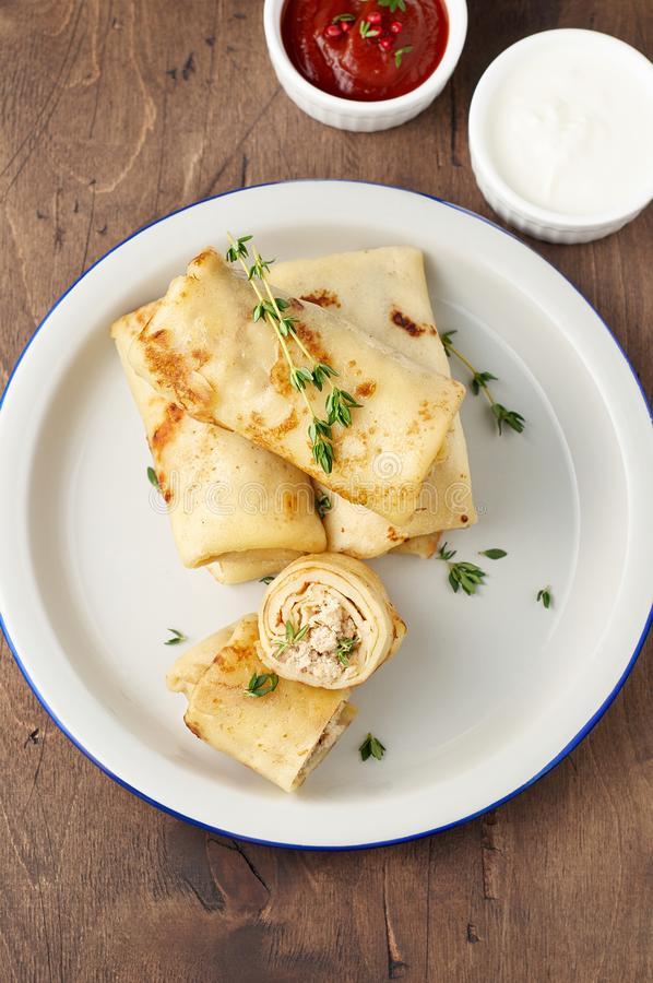 Savory crepe rolls with ground meat filling served with sour cream and tomato sauce stock images
