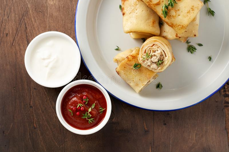 Savory crepe rolls with ground meat filling served with sour cream and tomato sauce royalty free stock image