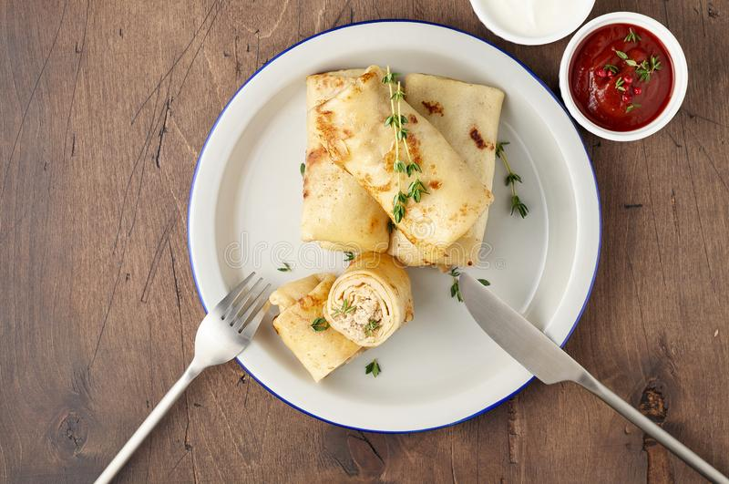 Savory crepe rolls with ground meat filling served with sour cream and tomato sauce royalty free stock photography