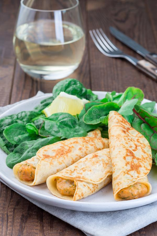 Savory crepe with shrimps and creamy dill sauce served with green leaves salad and lemon, vertical royalty free stock image