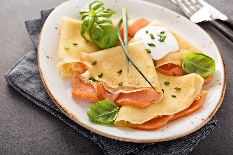 Savory crepes with salmon filling. And sour cream stock images