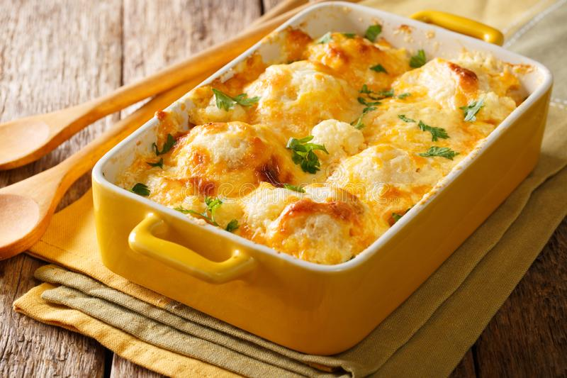 Savory food: baked cauliflower with cheese, eggs and cream close. Up in a baking dish on a table. horizontal royalty free stock photos