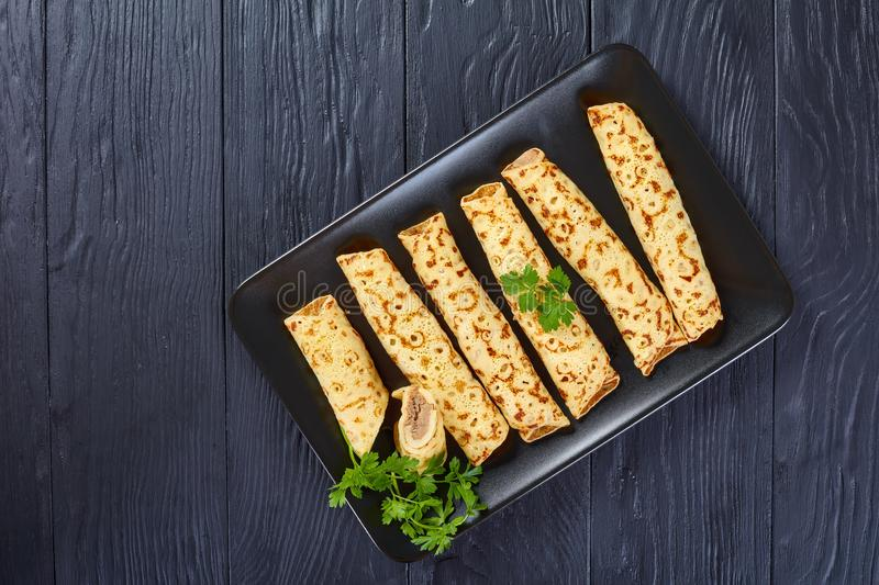 Chicken cheese pate stuffed crepes, top view. Savory Homemade chicken cheese pate stuffed crepes with fresh parsley leaves on a black plate on a black wooden royalty free stock photos