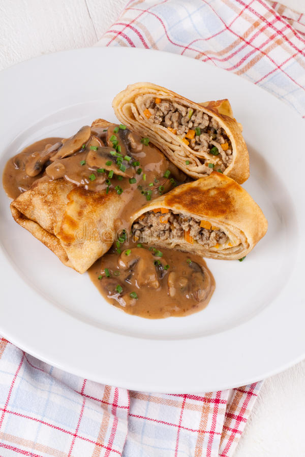 Savory mince pancakes or tortillas. Cut open to show the ground or minced meat and vegetable filling in a rich tasty gravy royalty free stock image