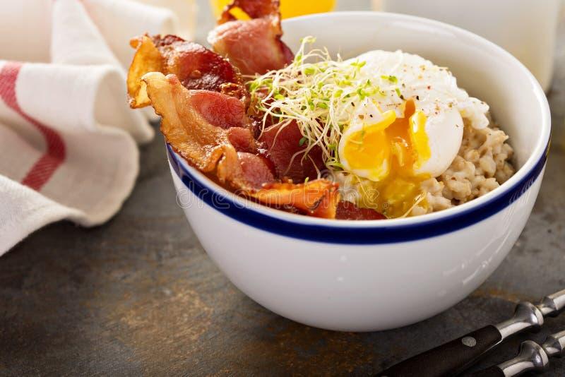 Savory oatmeal porridge with egg and bacon. Savory oatmeal porridge with poached egg and bacon stock photo