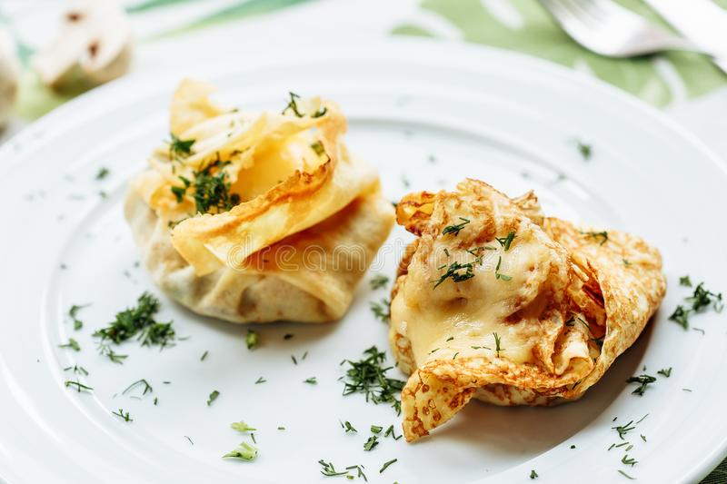 Savory pancake like cake filled with mushrooms and ham on white plate with green dill stock photo