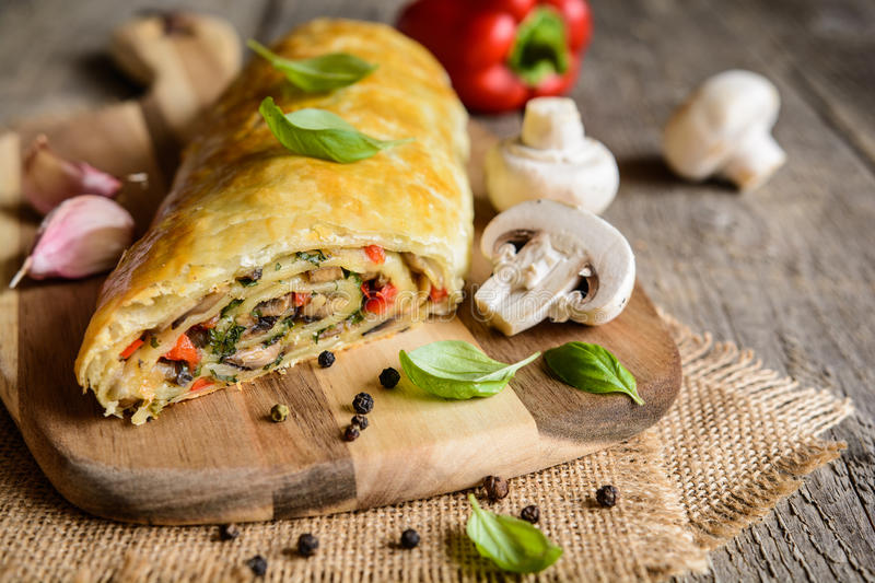 Savory strudel with mushrooms, red pepper, onion, garlic and parsley. Vegetable savory strudel stuffed with mushrooms, red pepper, onion, garlic and parsley royalty free stock photo