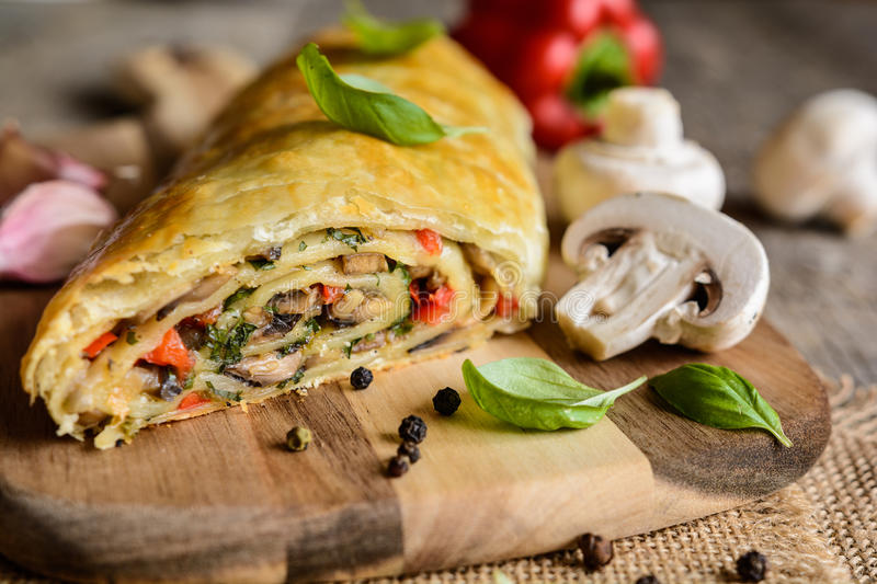 Savory strudel with mushrooms, red pepper, onion, garlic and parsley. Vegetable savory strudel stuffed with mushrooms, red pepper, onion, garlic and parsley stock photography