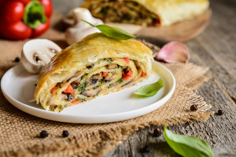 Savory strudel with mushrooms, red pepper, onion, garlic and parsley. Vegetable savory strudel stuffed with mushrooms, red pepper, onion, garlic and parsley stock images