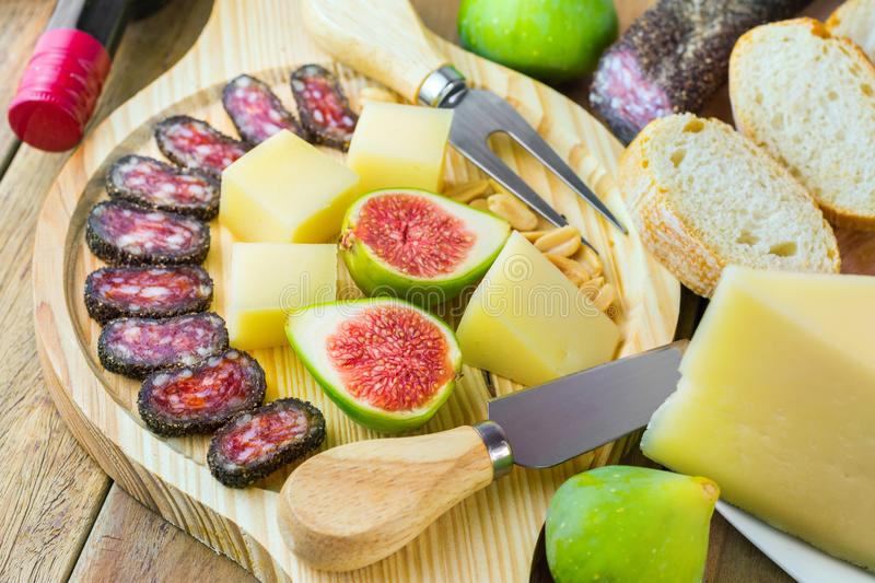 Savory and sweet snack and appetizers board with variety of meat charcuterie cheese nuts fresh figs french baguette royalty free stock photography