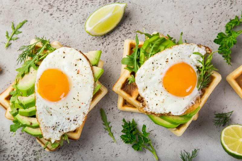 Savory waffles with avocado, arugula and fried egg for breakfast. Top view stock photos