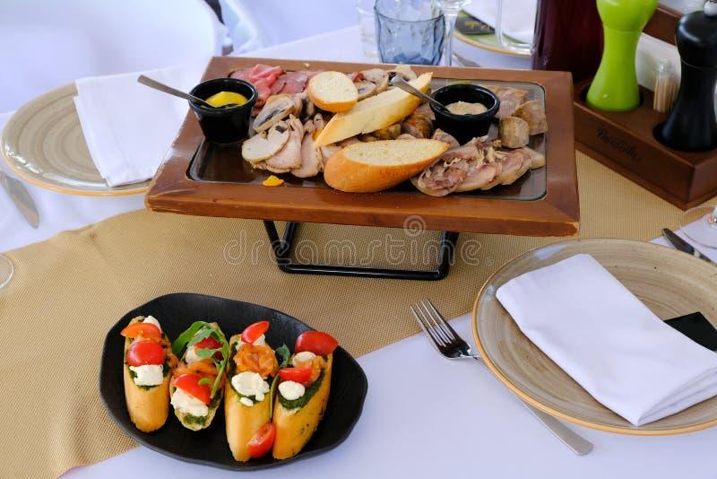 Savoureux fumé a coupé en tranches le lard sur un plateau en bois sur une table de banquet dans un restaurant image stock