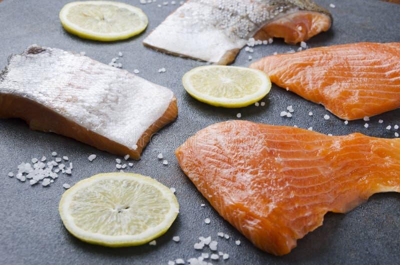 Savoureux plusieurs morceaux de saumons avec le citron, seasalt sur la table grise Cuisson de la préparation photos libres de droits