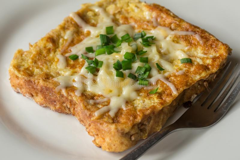 Savoury French toast topped with chopped green spring onions and melted cheese stock photo