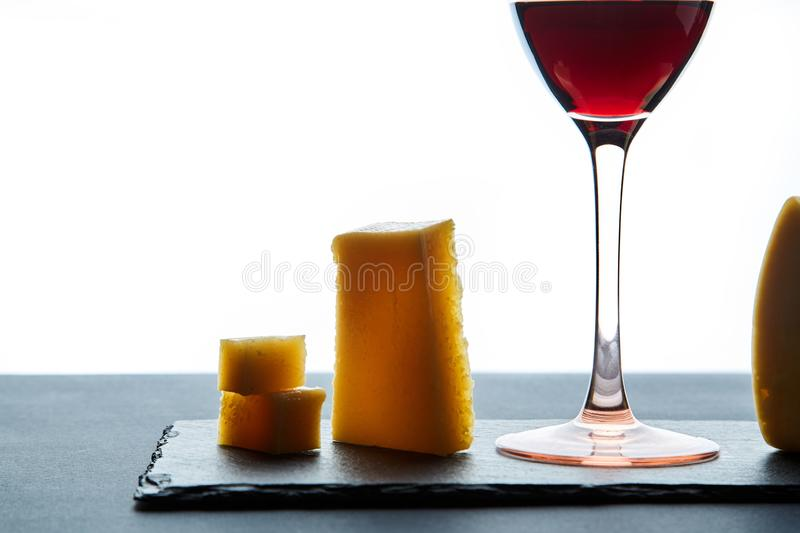 Savoury hard cheese beside glass of sweet red wine on white background royalty free stock images