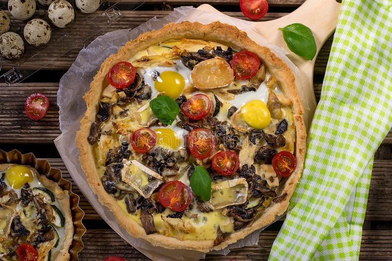 Savoury open pastry tart quiche with zucchini, mushrooms, tomato and quail eggs royalty free stock photography