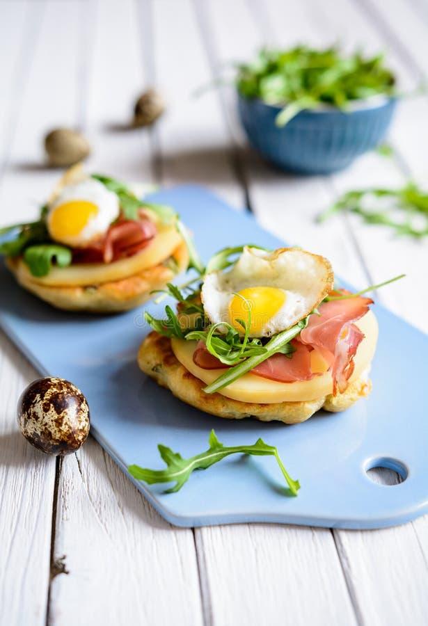 Savoury yoghurt and scallion pancakes with Black Forrest ham, smoked cheese, quail egg and arugula stock photos