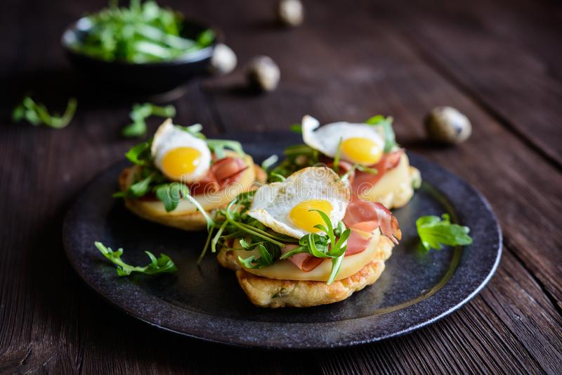 Savoury yoghurt and scallion pancakes with Black Forrest ham, smoked cheese, quail egg and arugula royalty free stock images
