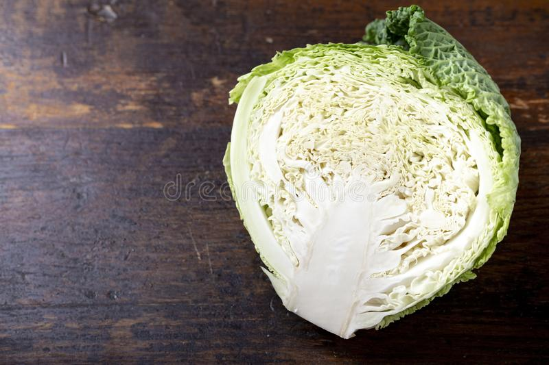 Savoy cabbage cut in half. One half of savoy cabbage on brown wooden background royalty free stock photography