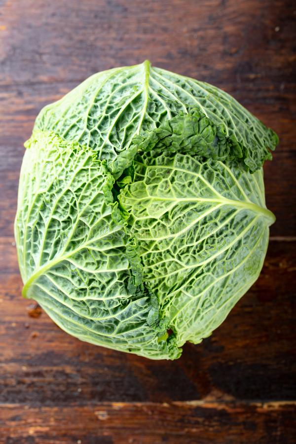Savoy cabbage head. Head of savoy cabbage on wooden background. space for text stock photos