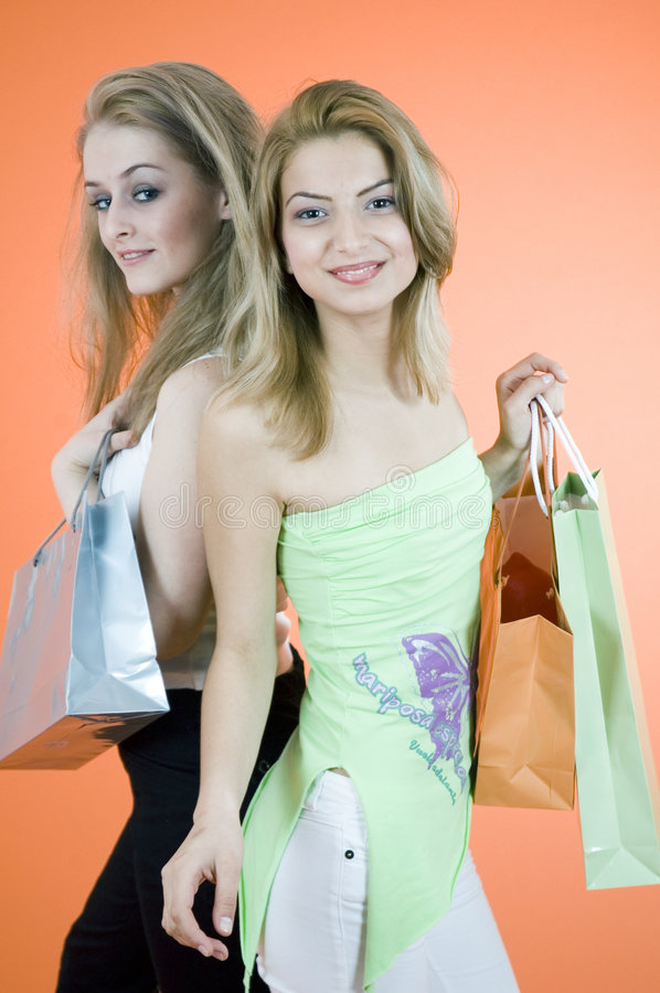 Savvy Shoppers. Two women with confident expressions holding multiple shopping bags. Taken in studio with orange background royalty free stock photos