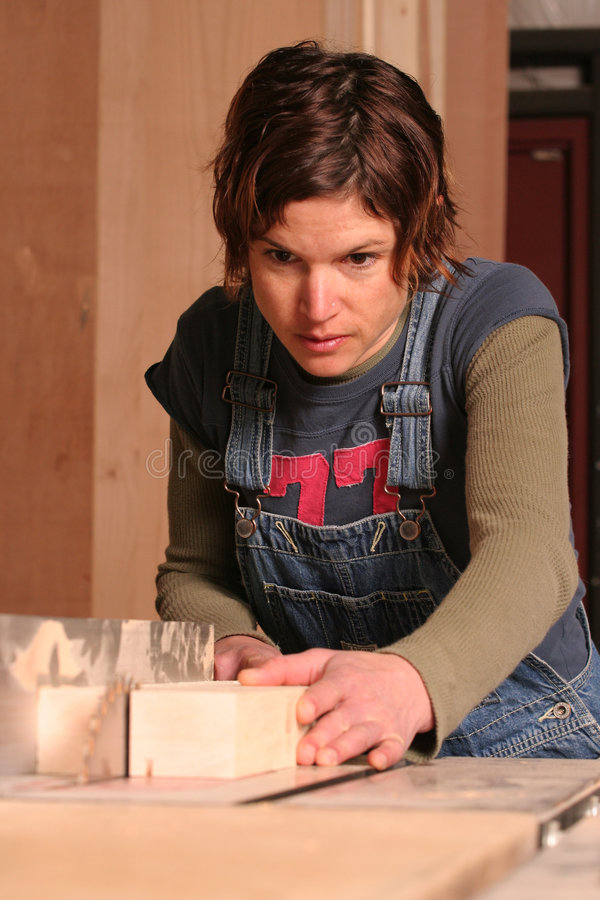 Saw. A female woodworker rips a piece of wood in a wood shop royalty free stock image