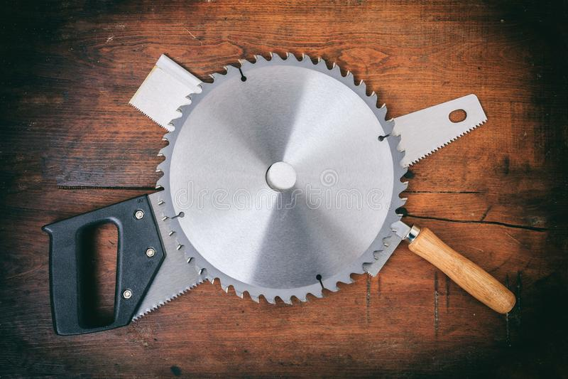 Saw blade and hand saws on wooden background stock photo