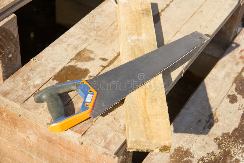 Saw and board - construction tools stock images