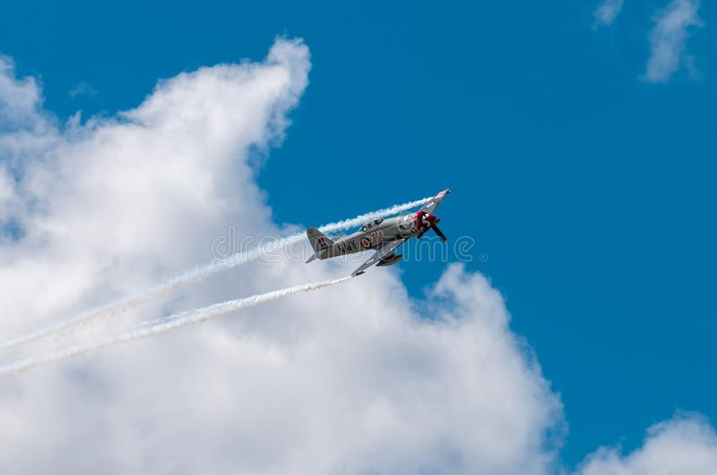 Sawbones Turns Against Clouds. EDEN PRAIRIE, MN - JULY 16 2016: Hawker Sea Fury FB-11f turns against clouds at air show. The Sea Fury was a British fighter royalty free stock photography