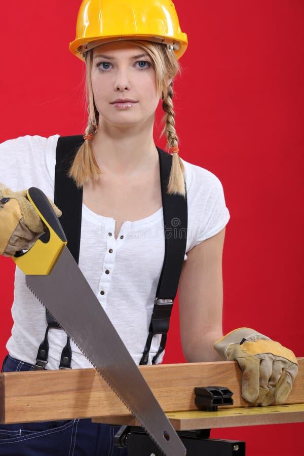 Sawing fêmea do carpinteiro. fotografia de stock