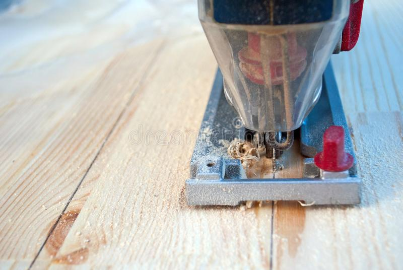 Sawing wood with a jigsaw royalty free stock image
