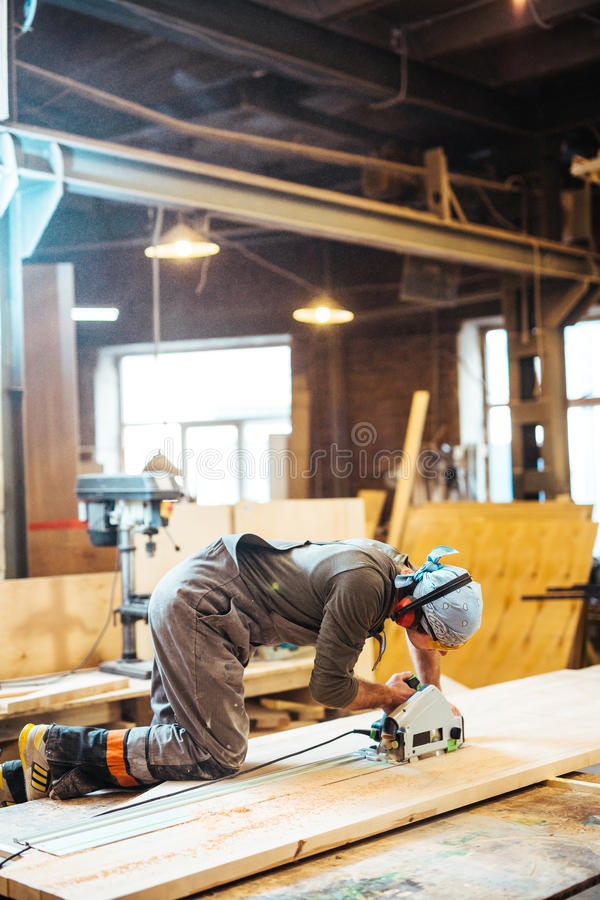 Sawing wood. Modern joiner with scroll-saw working with wood royalty free stock photo