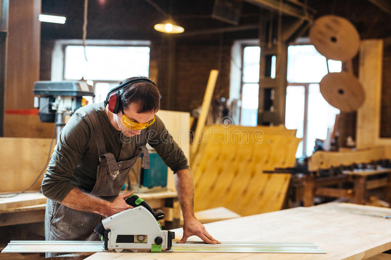 Sawing in workroom. Man in protective eyeglasses and headphones cutting wooden plank on workbench royalty free stock photography