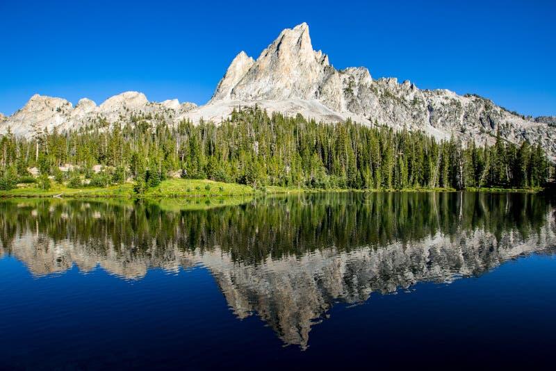 Sawtoothberg reflekterade i Alice Lake, Idaho royaltyfria foton