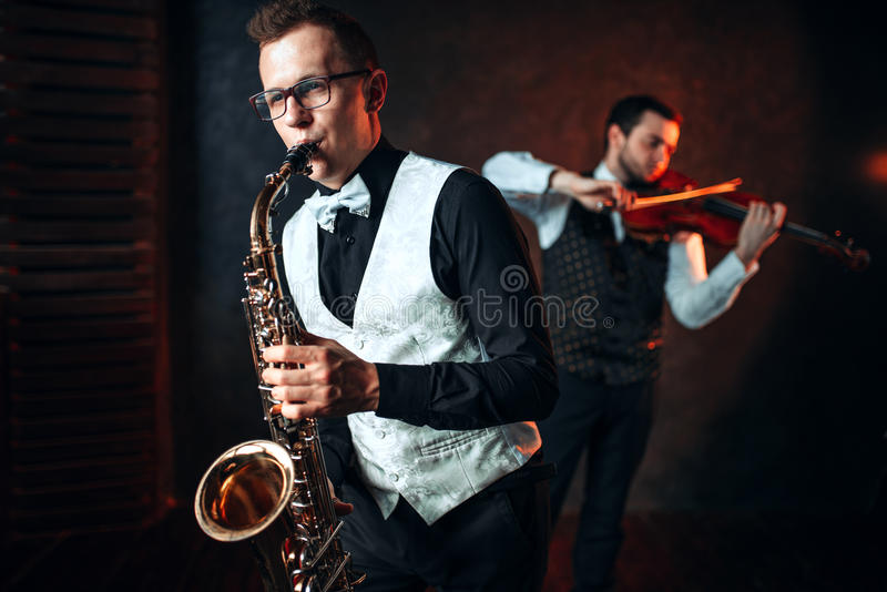 Sax man and fiddler duet playing classical melody. Sax men and fiddler duet playing classical melody. Jazz men and violinist royalty free stock images