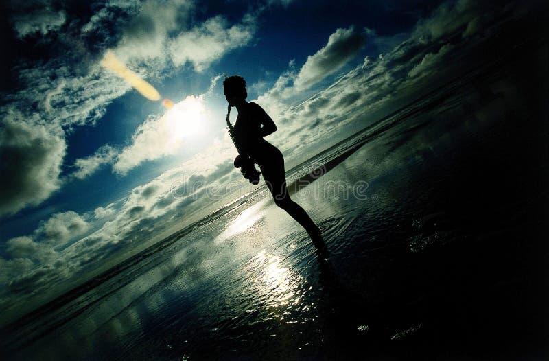 Saxofón atractivo del mar en la puesta del sol foto de archivo libre de regalías
