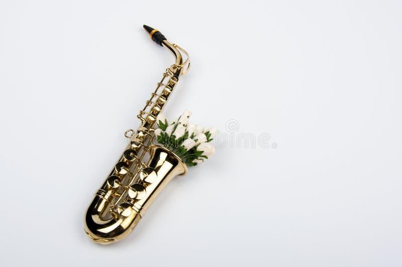 Saxofon med blommor royaltyfri foto