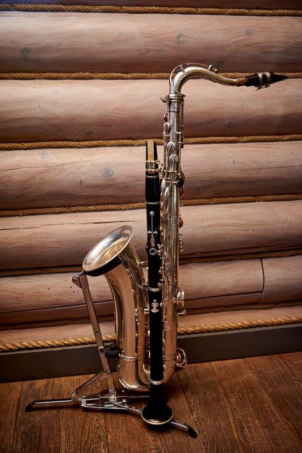 Saxofon och klarinett på en ställning mot royaltyfri foto