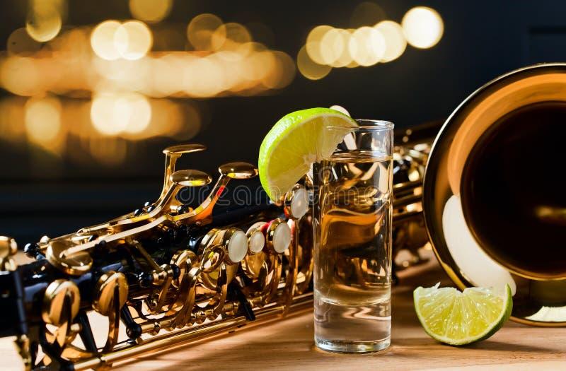 Saxofon och tequila med limefrukt royaltyfri foto