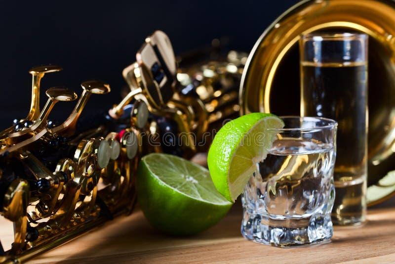 Saxofon och tequila med limefrukt fotografering för bildbyråer