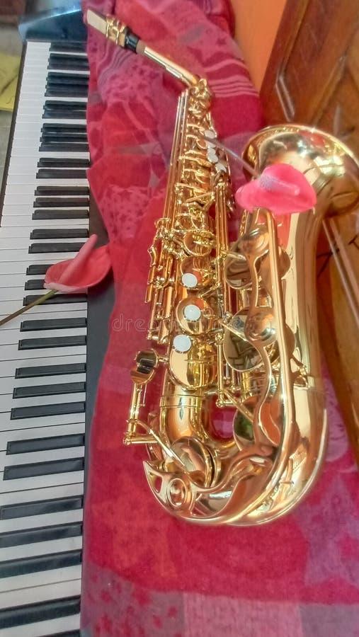Saxofon på pianot royaltyfria bilder