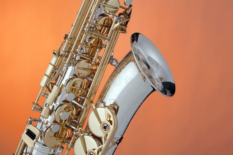 Saxofone do alto isolado na laranja foto de stock