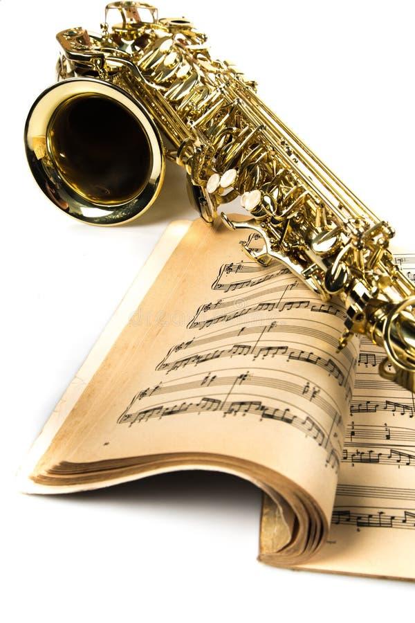 Saxofone no close-up do livro de notas da música imagem de stock