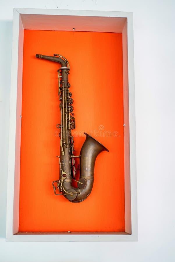 Saxofone no fundo alaranjado da cor imagens de stock