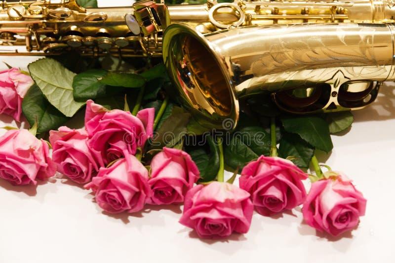Saxofonen med rosor stänger sig upp royaltyfria bilder