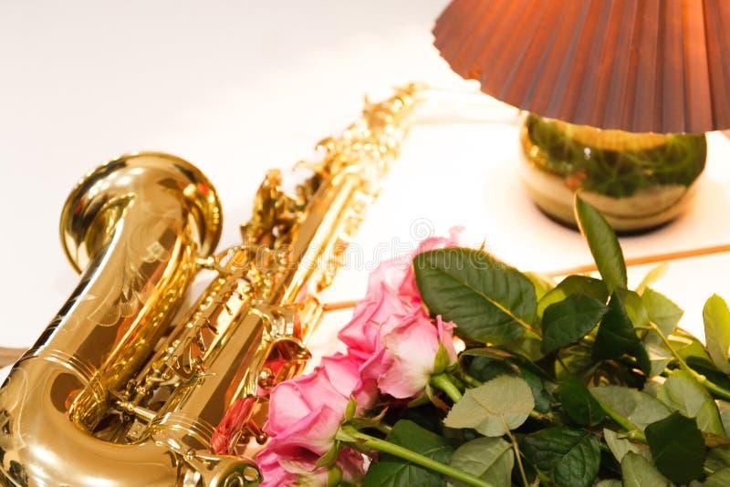 Saxofonen med rosor stänger sig upp royaltyfri bild