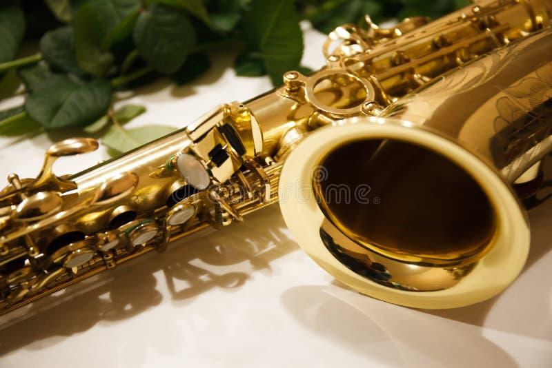 Saxofonen med rosor stänger sig upp royaltyfria foton